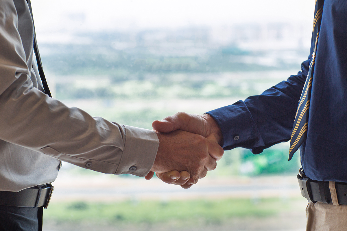Closeup of two businessmen shaking hands with blurry city view in background. People are seen partly.